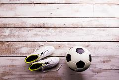 Soccer ball, cleats on white wooden floor, studio shot Stock Photos