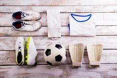 Soccer ball,cleats and various football stuff, wooden background Stock Photos