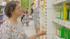 Young woman choosing cleanser in shop Stock Footage