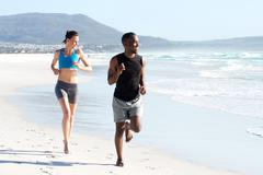 Healthy active couple running by water on the beach Stock Photos