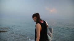 Young woman walking on a sandy beach of Mediterranean Sea during sunset - stock footage