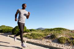Fitness male model running at the beach - stock photo