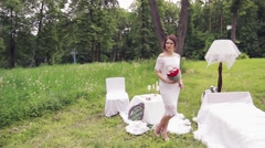 The bride in a white dress and red bouquet in the decoration Stock Footage