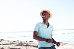 Cheerful young african man enjoying at the beach Stock Photos