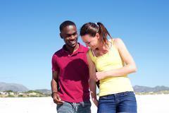 Young couple walking together on the beach - stock photo