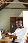 Young african american man sitting at table with mobile phone - stock photo