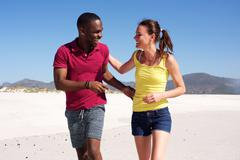 Happy young fitness couple walking together on beach - stock photo
