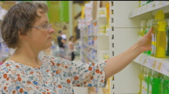 Woman buys cleaning products in a supermarket Stock Footage