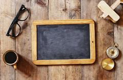 blank blackboard on wooden table. Top view - stock photo