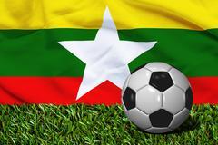 Soccer Ball on Grass with Myanmar Flag Background, 3D Rendering Stock Illustration