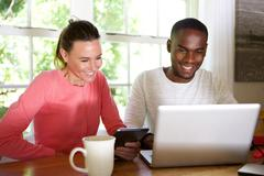 Mixed race couple using wireless technology at home - stock photo