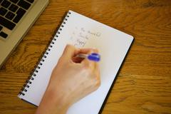 Female hand writing on notebook Stock Photos
