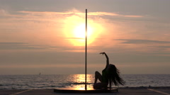 Silhouette of girl dancer performing fitness pole dance on the beach at sunset - stock footage