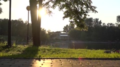 Slow motion steadicam clip of sunset park and runner entering and leaving frame - stock footage