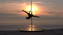 Strong woman doing pole dancing fitness exercise on the beach in summer evening - stock footage