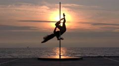 Spinning silhouette of girl pole dancer against the glowing sun Stock Footage