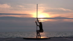 Strong girl performs fitness pole dance on the beach at sunset - stock footage