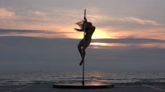 Fitness pole dance performance on portable dancing stage on the beach at sunset - stock footage