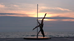 Fit girl poledancer performs advanced pole dance tricks on the beach at sunset - stock footage