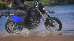Extreme driving a motorcycle. A skilled biker riding on the edge of water Stock Footage