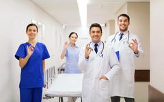 happy doctors with gurney showing ok at hospital - stock photo