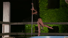 Slow motion dancer performs fitness pole dance on side of private pool at night - stock footage
