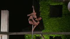 Slow motion of young woman performs fitness pole dance at night Stock Footage