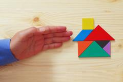 Man's hand pointing at house made from tangram puzzle Stock Photos