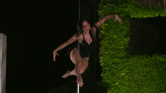 Fit girl poledancer performs fitness pole dance tricks at night outdoors - stock footage
