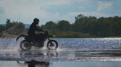 A romantic trip on a motorcycle. A skilled biker rides on the water's edge Stock Footage