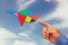 Man's hand pointing at plane made from tangram puzzle Stock Photos