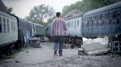 Solitary man walks past derelict trains in gloomy location - stock footage