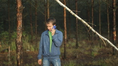 A man calling on the phone near a tree in the forest. Early morning Stock Footage