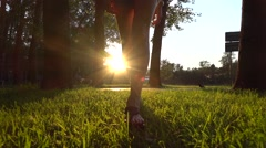 Slow motion steadicam shot of girl in sandals walking in summer sunset park Stock Footage