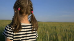 lovely little girl walking on the wheat field, back view, slow motion - stock footage