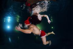Underwater fashion in the pool - stock photo