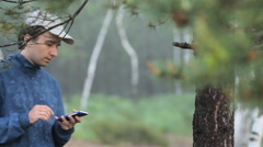 The man compose sms on the phone near a tree in the forest. Early morning - stock footage