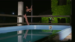 Young graceful woman reflected in water of pool performing fitness pole dance - stock footage