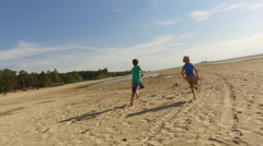 Boys playing with soccer ball on a beach - stock footage