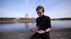 Young man getting message with tablet computer near the city lake Stock Footage