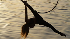 Silhouette of woman doing some acrobatic elements on aerial hoop - stock footage
