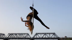 Beautiful woman doing acrobatic elements on aerial hoop hanging on a bridge Stock Footage