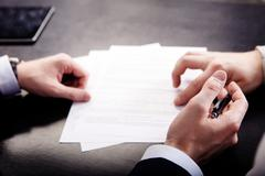 Closeup of male hand pointing where to sign a contract, legal papers or - stock photo