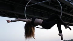 Beautiful woman doing some acrobatic elements on aerial ho hanging on the bridge Stock Footage
