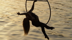 Silhouette of woman sitting on aerial hoop above the water Stock Footage