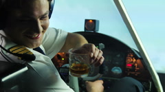 Crazy pilot drinking alcohol in cockpit and navigating plane, dangerous maniac - stock footage
