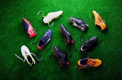 Various cleats against green artificial turf, studio shot Stock Photos