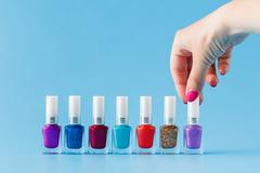 Group of bright nail polishes and woman hand Stock Photos