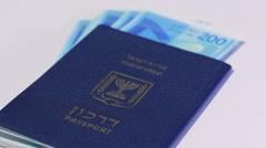 Rotating israeli money bills of 200 shekel and israeli passport Stock Footage