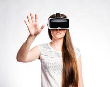 Woman with virtual reality goggles. Studio shot, gray background Stock Photos